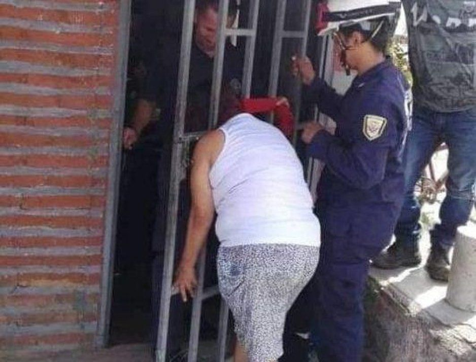 Vecina se queda atorada en una puerta por andar de metiche