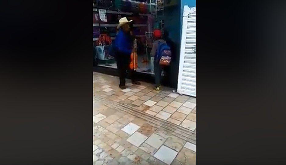 ¡INDIGNANTE! Empleado gandalla de tienda de Tehuacán moja a abuelito que tocaba el violín con su nieto (VIDEO)