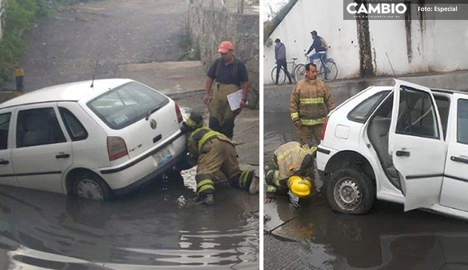 Se abre tremendo socavón en Texmelucan por fuertes lluvias, un auto se quedó atorado