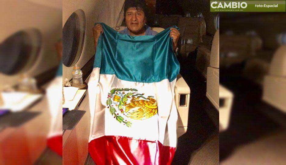 Posa Evo Morales con bandera de México en el avión que lo traslada