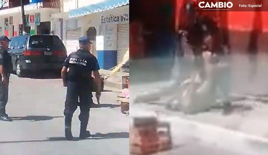 Policía municipal de Juan Galindo desenfunda su arma para retirar botes de apartados en la vía pública (VIDEO)