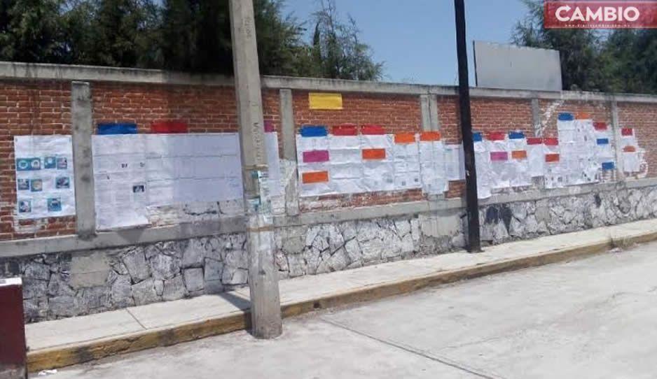 Jóvenes de secundaria pegan tareas en la barda de su escuela en Juan C Bonilla